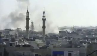 This image made from amateur video released by the Shaam News Network and accessed on Tuesday, April 17, 2012, purports to show smoke rising from buildings in Homs, Syria. (AP Photo/Shaam News Network via AP Video)