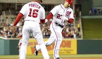 Washington Nationals third base coach Bo Porter congratulates Xavier Nady after he hit a home run during the eighth inning against the Cincinnati Reds on Friday, April 13, 2012, in Washington. The Nationals won 2-1 in 13 innings. (AP Photo/Evan Vucci)