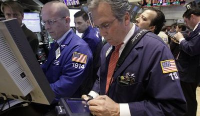 ** FILE ** Specialist Dermot Bermingham (second from left) and trader Thomas Kay (foreground at right) work on the floor of the New York Stock Exchange on Tuesday, April 17, 2012. (AP Photo/Richard Drew)