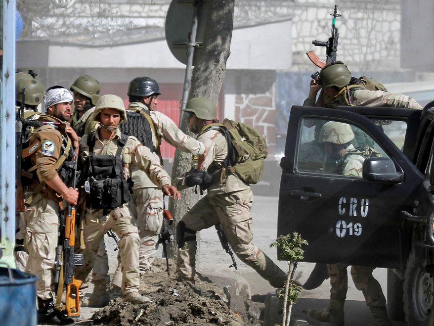 Afghan security forces rush to a battle in Kabul on Sunday, when militants launched a series of coordinated attacks across the city. The militant group Hizb-i-Islami, which walked out of peace talks last month, returned after their attack was foiled. (Associated Press)