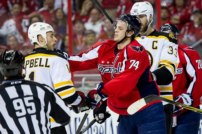 Boston Bruins center Gregory Campbell (11), left, and Washington Capitals defenseman John Carlson (74) get physical after a play in the first period as the Washington Capitals take on the Boston Bruins in game four of National Hockey