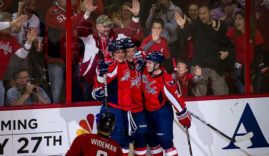 Washington Capitals teammates celebrate as Caps left wing Alexander Semin (28) (second from left) scores to bring the Capitals up 2-1 in the second period as Washington took on the Boston Bruins in game four of the National Hockey League's first-round playoffs at the Verizon Center in Washington on Thursday, April 19, 2012. (Andrew Harnik/The Washington Times)