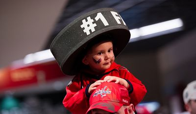 Aiden Witmer, 2, of Alexandria sits on the shoulders of his dad, Josh, on the way to their seats before the Washington Capitals took on the Boston Bruins in game four of the National Hockey League's first-round playoffs at the Verizon Center in Washington on Thursday, April 19, 2012. (Andrew Harnik/The Washington Times)