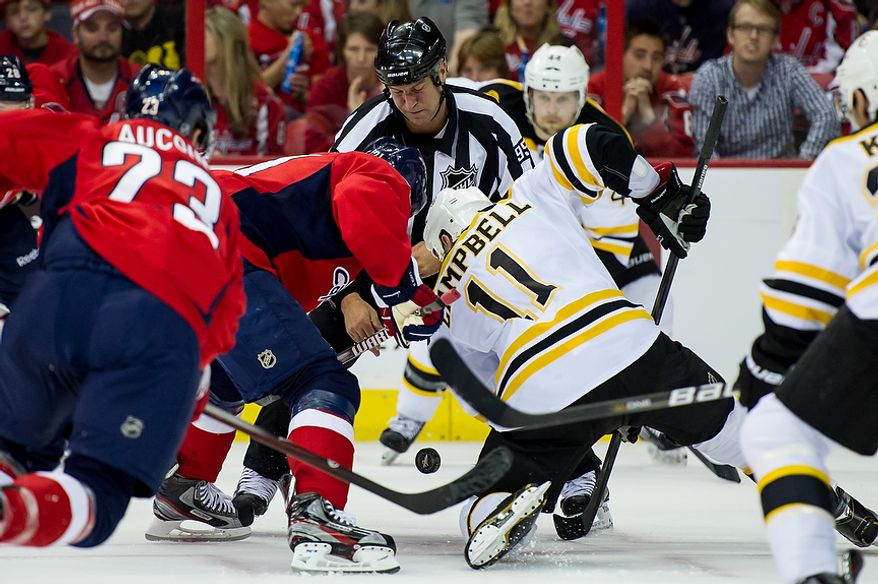 Washington Capitals center Brooks Laich (21) and Boston Bruins center Gregory Campbell (11) fight for the puck during a faceoff in the first period as the Caps took on the Bruins in game four of the National Hockey League's first-round playoffs at the Verizon Center in Washington on Thursday, April 19, 2012. (Andrew Harnik/The Washington Times)