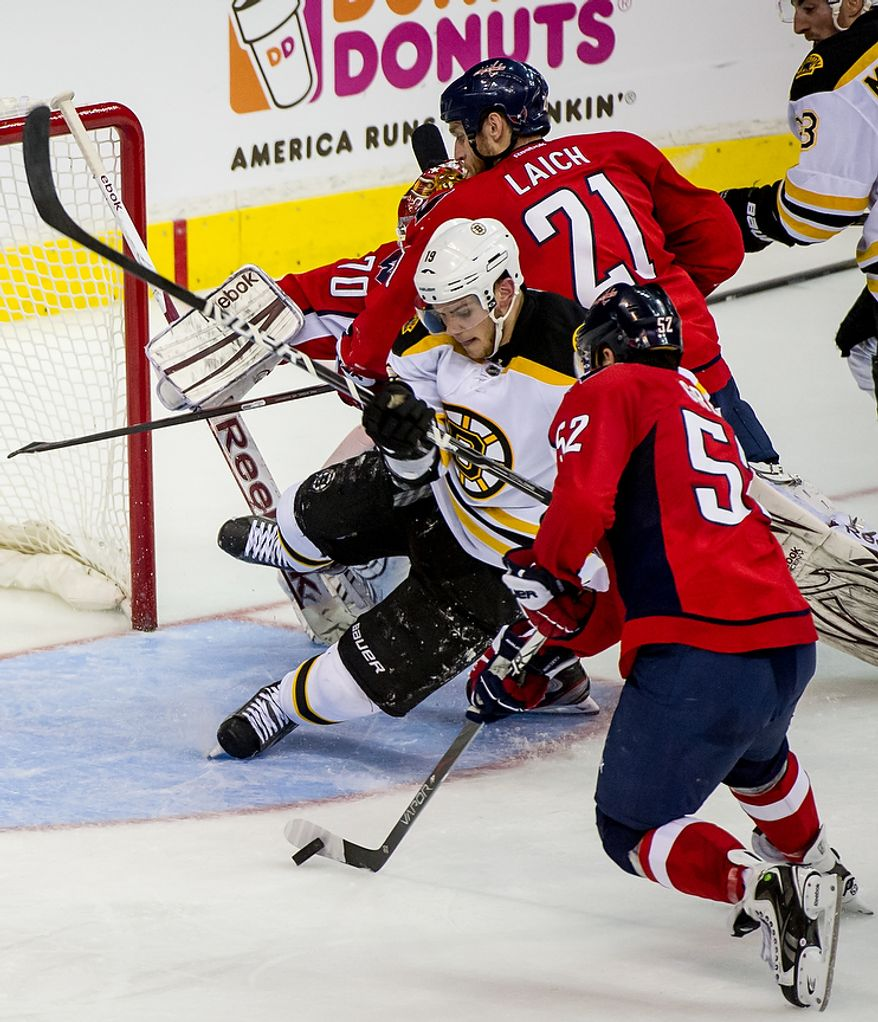 Washington Capitals defenseman Mike Green (52) (right) clears the puck from an open goal before Boston Bruins center Tyler Seguin (19) can get there in the second period as the Caps took on the Bruins in game four of the National Hockey League's first-round playoffs at the Verizon Center in Washington on Thursday, April 19, 2012. (Andrew Harnik/The Washington Times)