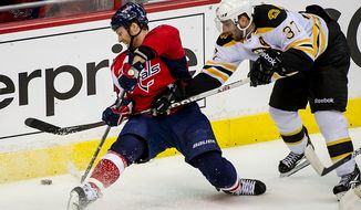 Washington Capitals defenseman Dennis Wideman (6) (left) goes down while battling for the puck against Boston Bruins center Patrice Bergeron (37) in the second period as the Caps took on the Bruins in game four of the National Hockey League's first-round playoffs at the Verizon Center in Washington on Thursday, April 19, 2012. (Andrew Harnik/The Washington Times)