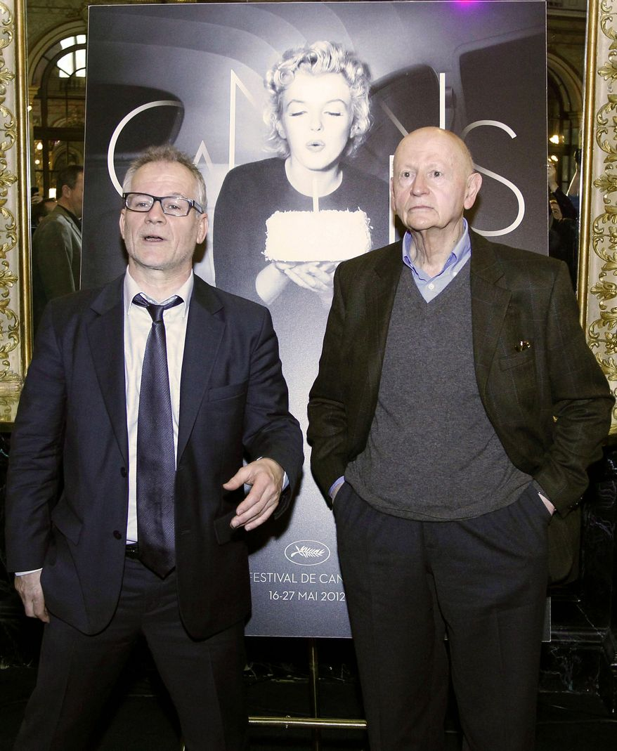 Gilles Jacob (left), president of the Cannes International Film Festival, and Artistic Director Thierry Fremaux pose in front of the poster for the festival's upcoming 65th edition, featuring American actress Marilyn Monroe, during a press conference in Paris on Wednesday, April 19, 2012, to announce this year's lineup. The festival will run May 16-27. (AP Photo/Francois Mori)