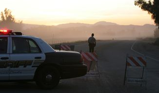 A deputy stands April 17, 2012, at a roadblock where a body was found near Lake Skinner near Winchester, Calif. Detectives searching for Brittany Dawn Killgore, who had been missing for four days, found the body after it was spotted by a maintenance worker leaving the area after clearing brush. (Associated Press/The Press-Enterprise)