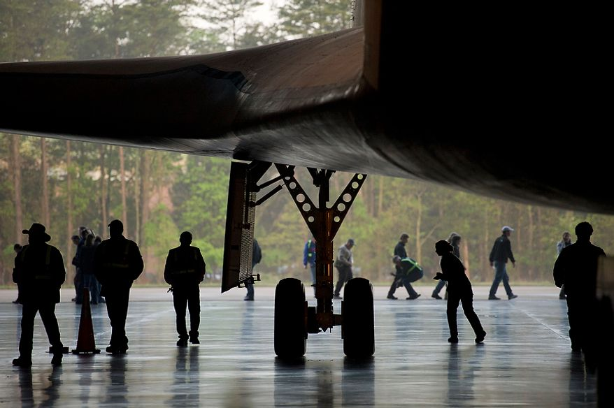 People prepare the NASA space shuttle Enterprise to be moved outside prior to the ceremonial arrival of the space shuttle Discovery at the National Air and Space Museum's Steven F. Udvar-Hazy Center in Chantilly, Va., on Thursday, April 19, 2012. (Rod Lamkey Jr./The Washington Times)