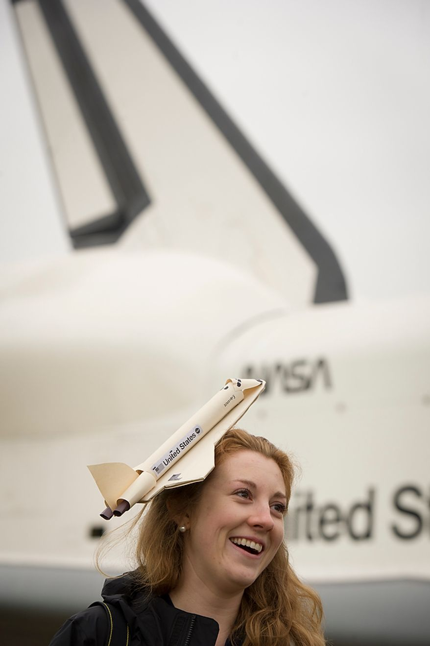 With the NASA space shuttle Enterprise in the background, Katherine Watson poses for a photo wearing her space shuttle hat before the ceremonial arrival of the NASA space shuttle Discovery at the National Air and Space Museum's Steven F. Udvar-Hazy Center in Chantilly, Va., on Thursday, April 19, 2012. (Rod Lamkey Jr./The Washington Times)