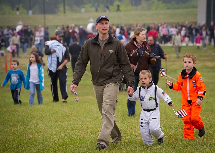 Chester Hull of Charlottesville, Va., walks with his two sons, Bryant (center), 4, and Cooper (right), 6, as they make their way to the ceremonial arrival of the NASA space shuttle Discovery at the National Air and Space Museum's Steven F. Udvar-Hazy Center in Chantilly, Va., on Thursday, April 19, 2012. (Rod Lamkey Jr./The Washington Times)