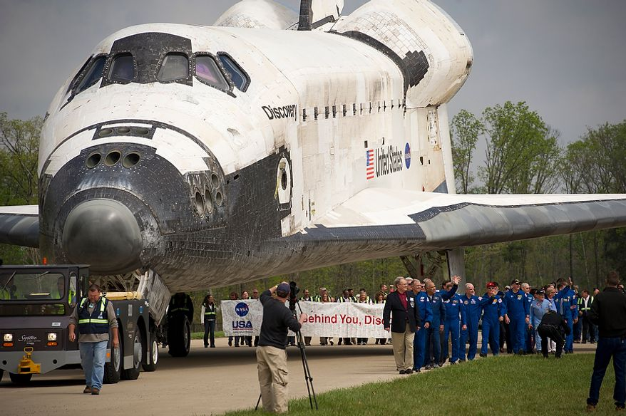 The NASA space shuttle Discovery is towed into place behind the stage to be used as a backdrop during the celebration of its arrival at the National Air and Space Museum's Steven F. Udvar-Hazy Center in Chantilly, Va., on Thursday, April 19, 2012. (Rod Lamkey Jr./The Washington Times)