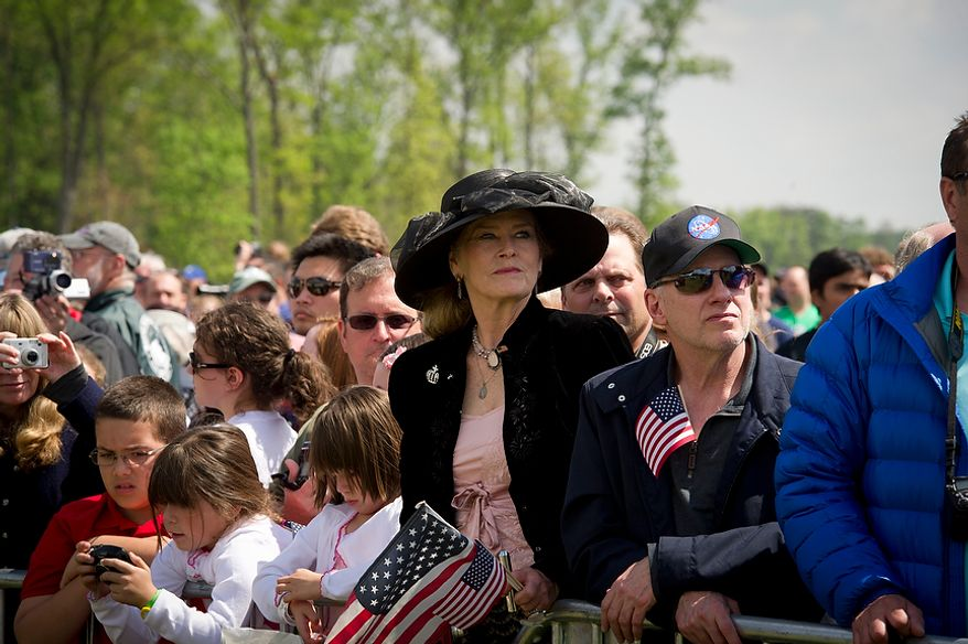 Cynthia Wood of Laurel, Md., holds her American flag as she watches the ceremonial arrival of the NASA space shuttle Discovery at the National Air and Space Museum's Steven F. Udvar-Hazy Center in Chantilly, Va., on Thursday, April 19, 2012. (Rod Lamkey Jr./The Washington Times)