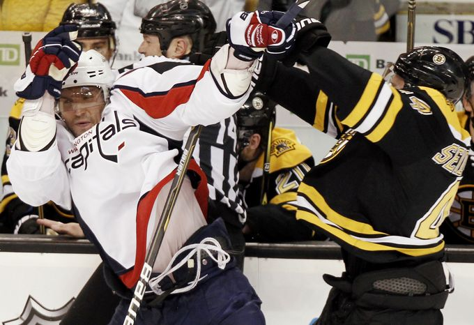 Washington Capitals' Alex Ovechkin, left, is hit by Boston Bruins' Dennis Seidenberg during the second period of Game 5 in a first-round NHL Stanley Cup playoff hockey series in Boston Saturday, April 21, 2012. (AP Photo/Winslow Townson)