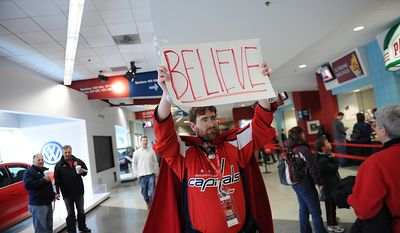 """Trevor White, of Silver Spring, Md., carries his """"Believe"""" sign among the crowd as the Washington Capitals host the Boston Bruins in the Eastern Conference Quarterfinals Game 6 at the Verizon Center in Washington, D.C., Sunday, April 22, 2012. (Rod Lamkey Jr/The Washington Times)"""