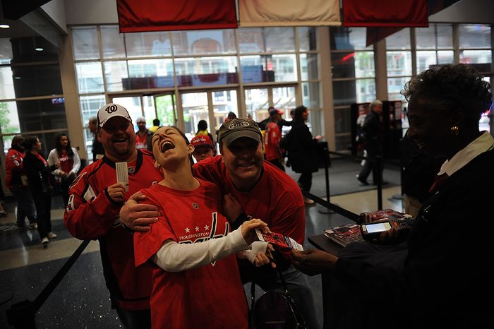 People laugh and pose for a quick photo as they arrive for the Eastern Conference Quarterfinals Game 6 between the Washington Capitals and the Boston Bruins at the Verizon Center in Washington, D.C., Sunday, April 22, 2012. (Rod Lamkey Jr