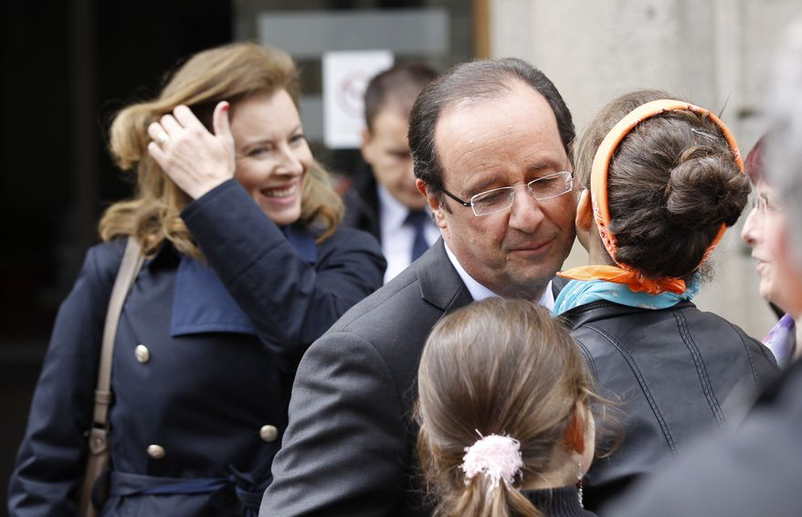 Francois Hollande, the Socialist Party candidate for French president, kisses a girl as he exits the town hall in Tulle, France, with his companion, Valerie Trierweiler (left), after voting in the first round of France's presidential election on Sunday, April 22, 2012. (AP Photo/Christophe Ena)