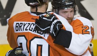 Philadelphia Flyers' Claude Giroux, right, and goalie Ilya Bryzgalov embrace after the Flyers defeated the Pittsburgh Penguins 5-1 in Game 6 of the first-round series, Sunday, April 22, 2012, in Philadelphia. The Flyers won the series 4-2. (AP Photo/The Courier-Post, Jose F. Moreno)
