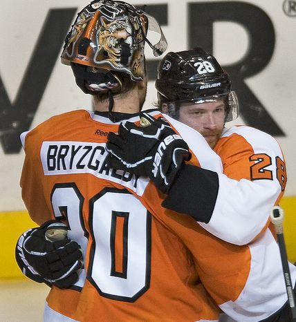 Philadelphia Flyers' Claude Giroux, right, and goalie Ilya Bryzgalov embrace after the Flyers defeated the Pittsburgh Penguins 5-1 in Game 6 of the first-round series, Sunday, April 22, 2012, in Philadelphi
