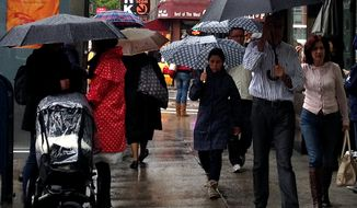 People walk with umbrellas in the rain along 9th Avenue in New York on April 22, 2012. (Associated Press)