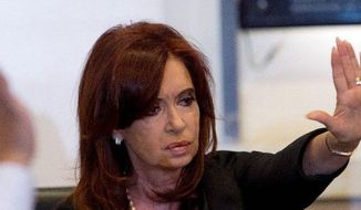 Argentine President Cristina Fernandez, motioning for silence as her YPF proposal is read at Government House in Buenos Aires, says it will restore Argentina's sovereignty, increase its oil production and lessen imports. (Associated Press)
