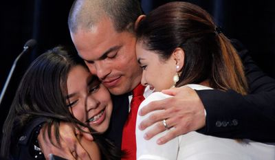 Former catcher Ivan Rodriguez hugs daughters Ivanna Sofia (left) and Amanda Christine at a news conference announcing his retirement in Arlington, Texazs. Rodriguez retired with the Rangers. (Associated Press)