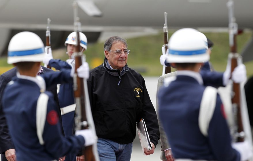 Defense Secretary Leon E. Panetta walks past an honor guard upon his arrival at the military airport in Bogota, Colombia, on Monday, April 23, 2012, on the first stop on his weeklong tour of Latin America. (AP Photo/Fernando Vergara)