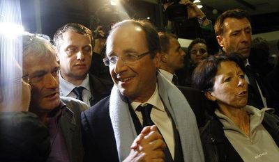 French Socialist presidential candidate Francois Hollande (center) arrives April 22, 2012, at Brive Airport in Brive, France, after the first round of the presidential election. (Associated Press)