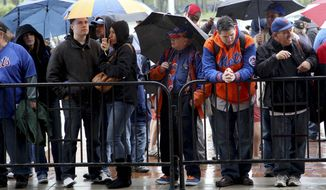 Fans stand in the rain and look through the gates into Citi Field after the Major League Baseball game between the New York Mets and San Francisco Giants was postponed because of weather on Sunday, April 22, 2012, in New York. (AP Photo/Seth Wenig)