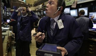 Trader Michael Zicchinolfi (right) works April 23, 2012, on the floor of the New York Stock Exchange. (Associated Press)