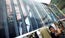 A protester holds a banner depicting one-time presidential candidates Omar Suleiman, Ahmed Shafik and Amr Moussa behind bars at a protest in Cairo's Tahrir Square on Friday. Of the three, only Mr. Moussa remains on the ballot; Mr. Suleiman and Mr. Shafik are among 11 disqualified by Egypt's electoral commission. (Associated Press)