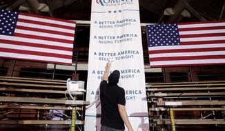 A worker irons a banner ahead of a rally for Mitt Romney, a GOP presidential candidate, in Manchester, N.H., on Tuesday. (Associated Press)