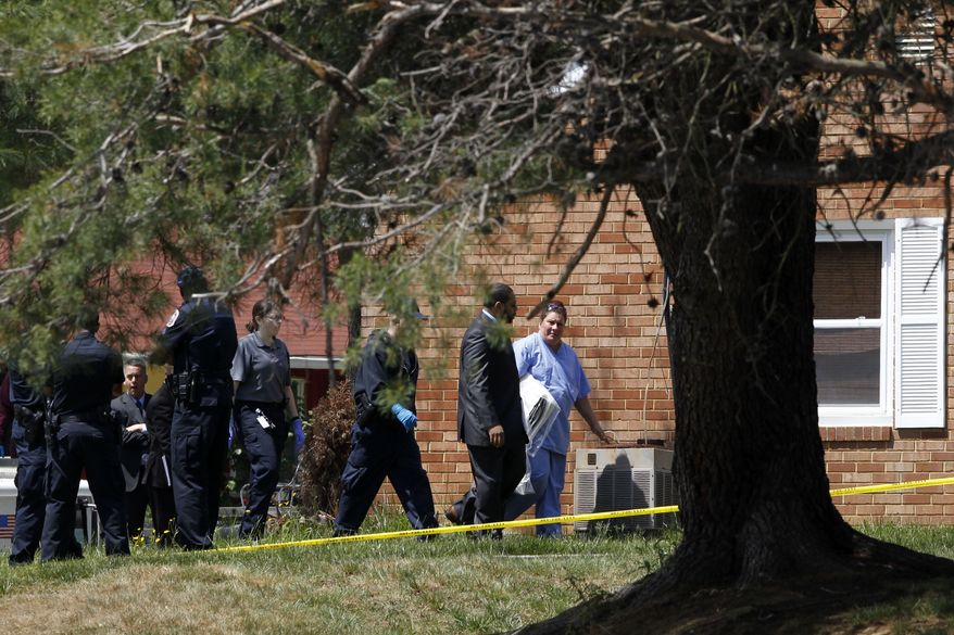 Investigators walk into an Oxon Hill home where bodies were found. Five people are dead of suspected carbon monoxide poisoning. (AP Photo/Charles Dharapak)
