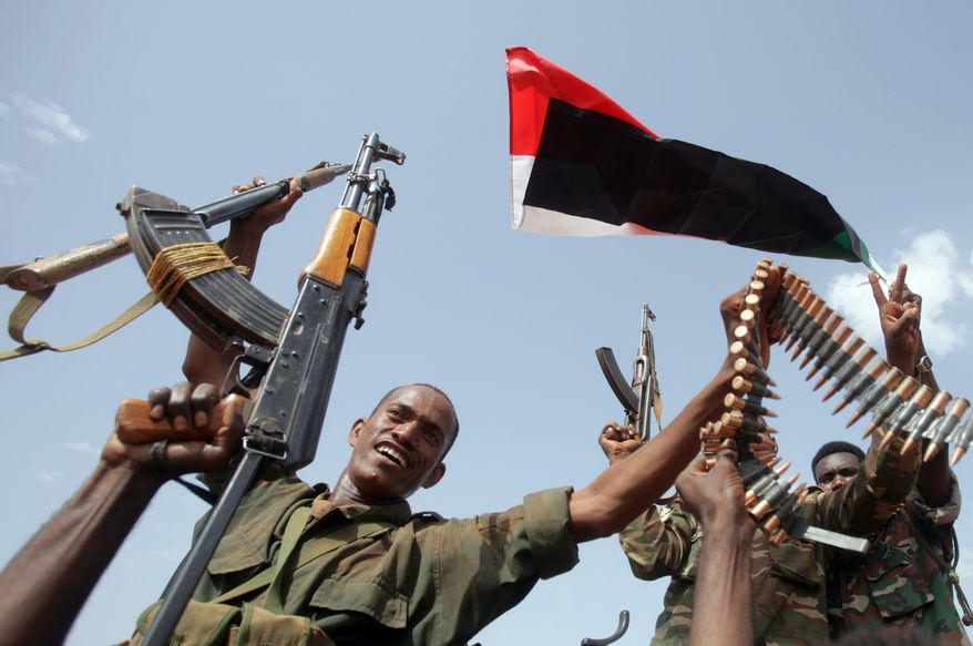 Members of the Sudanese armed forces raise their weapons during a visit by President Omar al-Bashir in Heglig, Sudan, on Monday, April 23, 2012. (AP Photo)