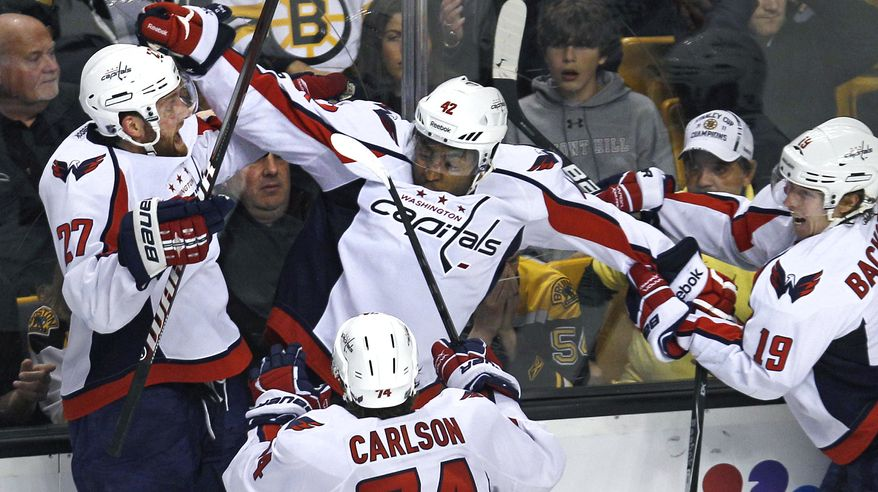 Washington Capitals right wing Joel Ward, center, is congratulated by teammates after his game-winning goal against the Boston Bruins during overtime of Game 7 of the first-round series in Boston on Wednesday, April 25, 2012. The Capitals won 2-1. (AP Photo/Charles Krupa)