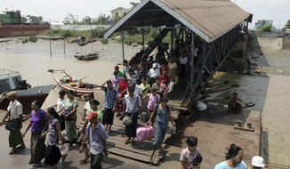 Passengers walk on a quay as they try to get on a ship to cross Yangon river in Yangon, Myanmar, on April 25, 2012. (Associated Press)
