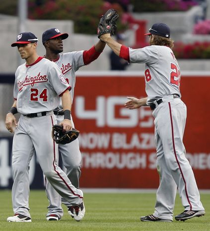 Washington Nationals' Roger Bernadina, second from left, and Jayson Werth, right, high-five behind Rick Ankiel (24) after defeating the San Diego Padres 7-2 on Wednesday, April 25, 2012, in San Diego. (AP Photo/Lenny Ignelzi)