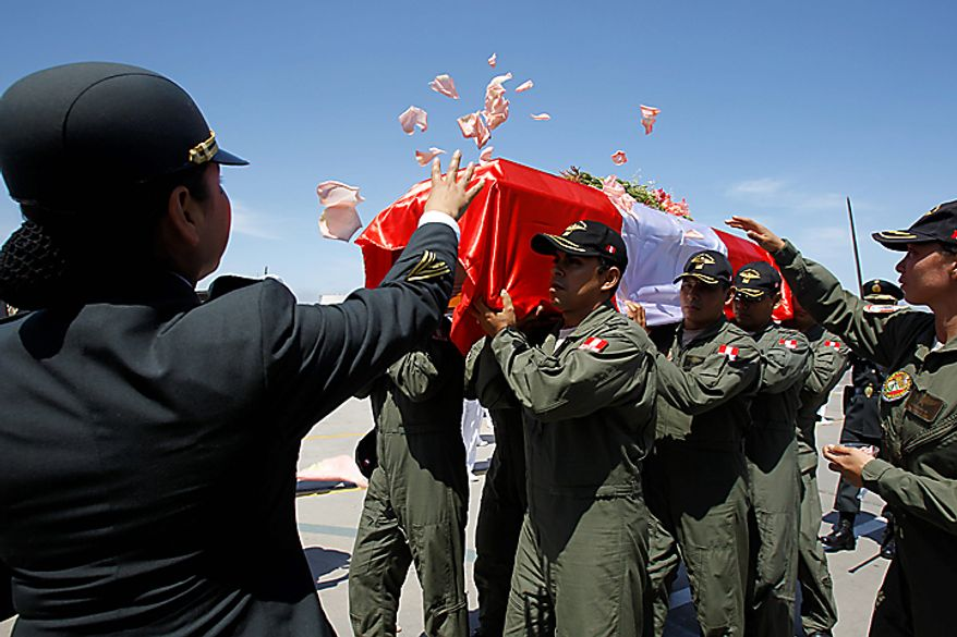 ** FILE ** Military officers carry the coffin containing the remains of police captain Nancy Flores at a police base in Callao, Peru, Friday April 13, 2012. Flores was killed while on board a helicopter that was searching for dozens of rebel-held hostages in Peru's Amazon jungle when it was attacked by gunfire Thursday. (AP Photo/Martin Mejia)