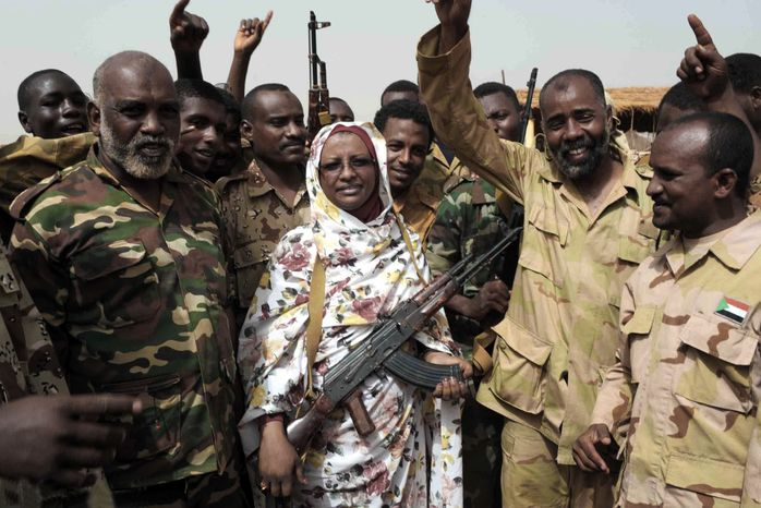 Sudanese state Minister of Information Sana Hamad poses April 24, 2012, for a photo with Sudanese armed forces at the oil-rich border town of Heglig, Sudan. (Associated Press)