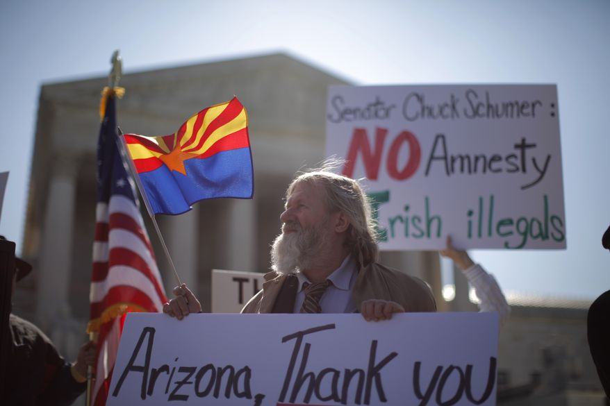 "** FILE ** Charles Balogh, from Alexandria, Va., demonstrates April 25, 2012, in front of the Supreme Court in Washington as the court holds a hearing on Arizona's ""show me your papers"" immigration law. (Associated Press)"