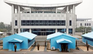 North Korean soldiers stand guard at the Demilitarized Zone that separates the two halves of the Korean Peninsula at Panmunjom, North Korea. The building in the background stands in the South. (Associated Press)