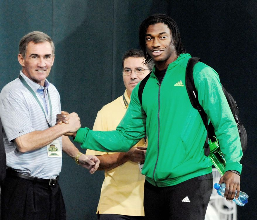 Griffin shakes hands with Washington Redskins coach Mike Shanahan as team owner Dan Snyder looks on during Baylor's pro day in Waco, Texas, last month. (Waco Tribune-Herald via Associated Press)