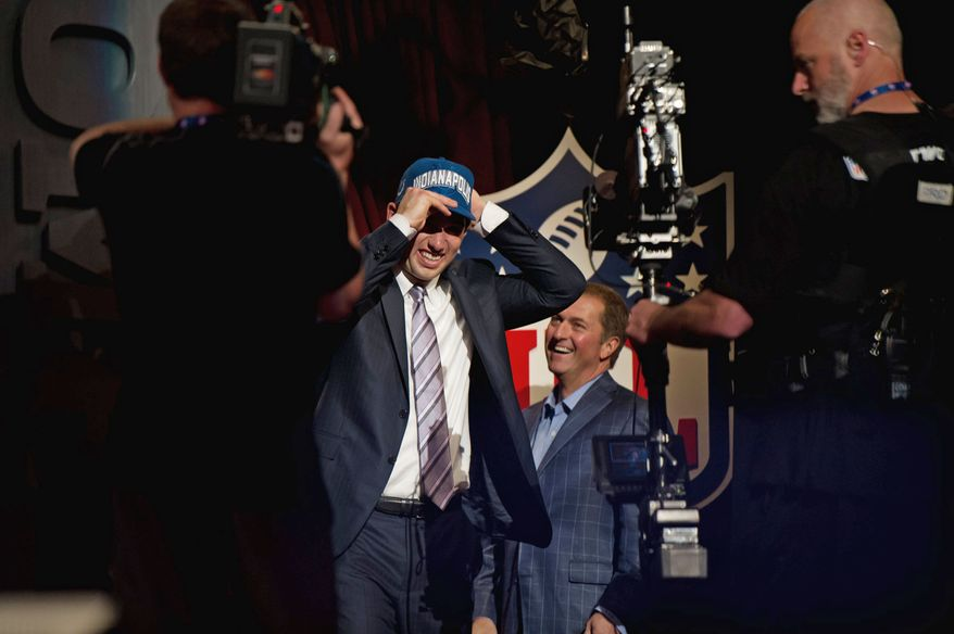 Former Stanford quarterback Andrew Luck slips on an Indianapolis Colts cap after being taken No. 1 overall in the NFL Draft at Radio City Music Hall in New York on Thursday night. (Andrew Harnik/The Washington Times)