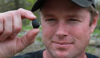 Robert Ward displays on April 25, 2012, one of two pieces of a meteorite he found at a park in Lotus, Calif. The meteor was probably about the size of a minivan when it entered the Earth's atmosphere three days earlier with a loud boom at about 8 a.m. (Associated Press)