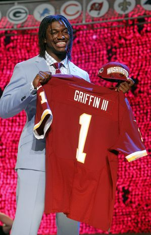 Baylor quarterback Robert Griffin III poses for photographs after he was selected as the second pick overall by the Washington Redskins in the first round of the NFL football draft at Radio City Music Hall, Thursday, April 26, 2012, in New York. (AP Photo/Jason DeCrow)