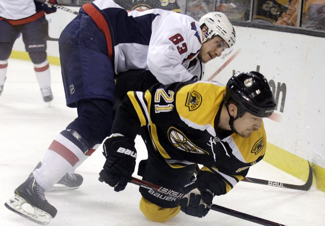 Washington Capitals center Jay Beagle checks Boston Bruins defenseman Andrew Ference as they compete along the boards for the puck during the first period of Game 7 the first-round playoff series in Boston on Wednesday, April 25, 2012. (AP Photo/Elise Amendola)