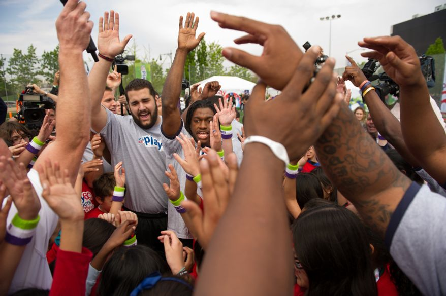 NFL draft prospects Robert Griffin III, center, and Matt Kalil, left, and 24 other NFL draft prospects cheer along with children while participating in a NFL Play 60 event to help teach the game of football to first through eighth grade New York City students held at Chelsea Waterside Park, New York, N.Y., Wednesday, April 25, 2012. (Andrew Harnik/The Washington Times)