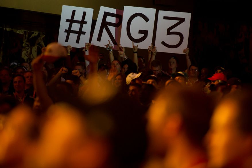 """Fans wave """"RG3"""" signs before Baylor quarterback Robert Griffin III is selected by the Washington Redskins as the second pick in the first round of the National Football League Draft held at Radio City Music Hall, New York, N.Y., Thursday, April 26, 2012. (Andrew Harnik/The Washington Times)"""