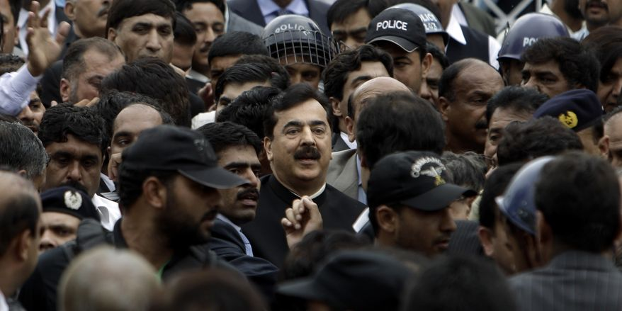 Pakistani Prime Minister Yousuf Raza Gilani (center), surrounded by guards, leaves the Supreme Court in  Islamabad on Thursday, April 26, 2012, after he was convicted of contempt for refusing to reopen an old corruption case against President Asif Ali Zardari. (AP Photo/Muhammed Muheisen)