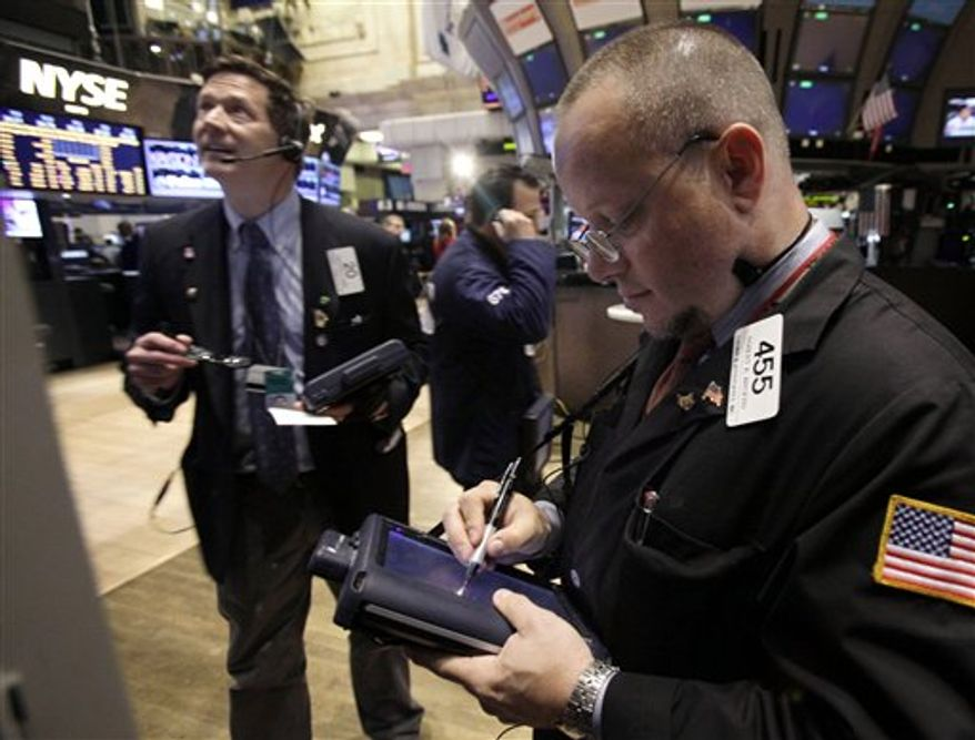 In an April 23, 2012 photo Robert Arciero, right, works with fellow traders on the floor of the New York Stock Exchange. Wall Street headed for a mixed opening Friday April 27, 2012, with Dow Jones industrial futures slipping marginally while the S&P 500 futures fell 0.1 percent (AP Photo/Richard Drew)